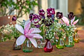 DESIGNER ANGELA COLLINS: RED AND GREEN GLASS JARS, CONTAINERS ON TABLE WITH MAGNOLIA AND TULIPS, FLOWER ARRANGEMENT, PURPLE, RED, PINK, FLOWERS, BLOOMS, APRIL, SPRING