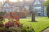 HALL O TH WOOD, CHESHIRE: HOUSE, LAWN, SPRING, APRIL, CLIPPED, TOPIARY, SHAPES, GREEN, YEW, TAXUS, MAPLE, ACERS, SCULPTURE ON LAWN
