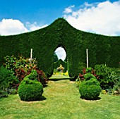 ARCHWAY IN SHAPED LEYLANDII HEDGE WITH TOPIARY IN FOREGROUND.  STOURTON HOUSE  WILTSHIRE
