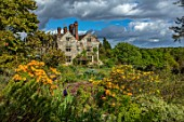 GRAVETYE MANOR, SUSSEX: COUNTRY GARDEN, APRIL, SPRING, AZALEAS, EVENING LIGHT, WOODLAND, NATURAL, NATURALISTIC, HILLSIDE, EUPHORBIAS, IRISES