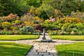 GRAVETYE MANOR, SUSSEX: COUNTRY GARDEN, APRIL, SPRING, PATHS, LAWNS, SLOPE, SLOPES, HILLS, HILLSIDE, AZALEAS, TUILPS, BORDERS, CARDOONS