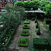 SQUARE BOX HEDGES & BOX DOMES. CONICAL BOX IN VERSAILLE TUBS IN AREA OF BRICKS & PAVING STONES. DESIGNER: VICTOR SHANLEY