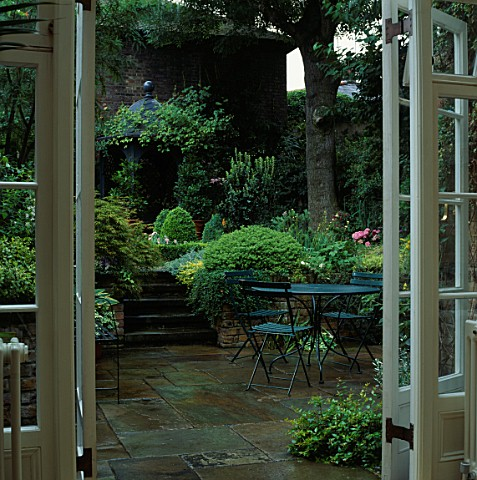 VIEW_THROUGH_FRENCH_WINDOWS_TO_PAVED_COURTYARD_DINING_AREA_STEPS_FLANKED_BY_LUSH_FOLIAGE_DESIGNER_JI