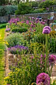 DESIGNER JAMES SCOTT, THE GARDEN COMPANY: RAISED BED, TERRACE, BORDER WITH ALLIUMS PURPLE SENSATION, GIGANTEUM, GLOBEMASTER, VIOLET BEAUTY, CHRISTOPHII, AUBRETIA DELTOIDEA, MAY