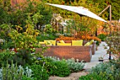 DESIGNER JAMES SCOTT, THE GARDEN COMPANY: TERRACE, RAISED BEDS, CORTEN STEEL EDGING, EDGES, BEDS, PRUNUS SERRULA, GEUM TOTALLY TANGERINE, CHAIRS, LOUNGERS