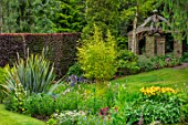 YORK GATE, YORKSHIRE: THE OLD ORCHARD, LAWN, PHORMIUM, BAMBOO, IRIS PSEUDACORUS VAR. BASTARDII, COPPER BEECH HEDGE, WOOD, BRICK PERGOLA, POLYGONUM BISTORTA SUPERBUM