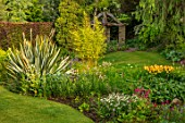 YORK GATE, YORKSHIRE: THE OLD ORCHARD, LAWN, IRIS PSEUDACORUS VAR. BASTARDII, POLYGONUM BISTORTA SUPERBUM, HEMEROCALLIS CORKY, POOL, POND, WATER, PHORMIUM, WOOD, STONE, PERGOLA