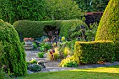 YORK GATE, YORKSHIRE: JUNE, SUMMER, TERRACE, PATIO, CONTAINERS WITH SUCCULENTS, CLIPPED, TOPIARY, HEDGES, HEDGING, YEW, LAWN, AEONIUM ZWARTKOP