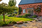 MORTON HALL, WORCESTERSHIRE: TERRACE, PAVING, ERIGERON ANNUUS, THYMES, THYMUS SERPHYLLUM RUSSETINGS, CLEMATIS, LAWN, JUNE, SUMMER