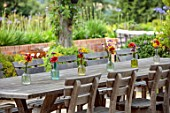 ALDERWOOD HOUSE, KENT: TERRACE, PATIO, WOODEN, TABLE, CHAIRS, GLASS JARS ON TABLE WITH GALLARDIA BURGUNDY, VERBENA BONARIENSIS, HELICHRYSUM ANGUSTIFOLIUM