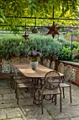 PRIVATE GARDEN, BERKSHIRE: DESIGNER ISTVAN DUDAS: PATIO, TERRACE, METAL TABLE, CHAIRS, BOX, PERGOLA, ARCHES, WISTERIA, HOSTAS, CONTAINER WITH HYDRANGEA