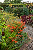 MORTON HALL GARDENS, WORCESTERSHIRE: KITCHEN GARDEN, CROCOSMIA OKOVANGO, FOENICULUM VULGARE GIANT BRONZE, JULY, BORDERS, KITCHEN, ARCH