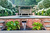 THE OLD VICARAGE, WORMINGFORD, ESSEX: DESIGNER JEREMY ALLEN - RILL GARDEN, WATER, WATERFALL, PYRUS SALICIFOLIA, BUXUS, HYDRANGEA ANNABELLE, HOSTAS, SEAT, BENCH, WOODEN PERGOLA