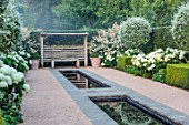 THE OLD VICARAGE, WORMINGFORD, ESSEX: DESIGNER JEREMY ALLEN - RILL GARDEN, WATER, PYRUS SALICIFOLIA, BUXUS, HYDRANGEA ANNABELLE, SEAT, BENCH, WOODEN PERGOLA, PERSICARIA POLYMORPHA