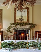 MARBURY HALL, SHROPSHIRE: DESIGNER SOFIE PATON-SMITH - DINING ROOM, FIREPLACE GARLAND OF HOPS, TABLE, CHAIRS, EUCALYPTUS TABLE DECORATION, CANDLES, DECEMBER