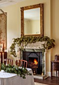 MARBURY HALL, SHROPSHIRE: DESIGNER SOFIE PATON-SMITH - DINING ROOM, FIREPLACE GARLAND OF HOPS, TABLE, CHAIRS, EUCALYPTUS TABLE DECORATION, CANDLES, MIRROR, DECEMBER