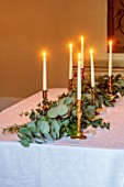 MARBURY HALL, SHROPSHIRE: DESIGNER SOFIE PATON-SMITH - DINING ROOM, CHRISTMAS, TABLE, GARLAND OF EUCALYPTUS, ROSEMARY, CANDLES, DECEMBER