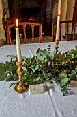 MARBURY HALL, SHROPSHIRE: DESIGNER SOFIE PATON-SMITH - DINING ROOM, CHRISTMAS, TABLE, GARLAND OF EUCALYPTUS, ROSEMARY, CANDLES, DECEMBER, NAME TAG